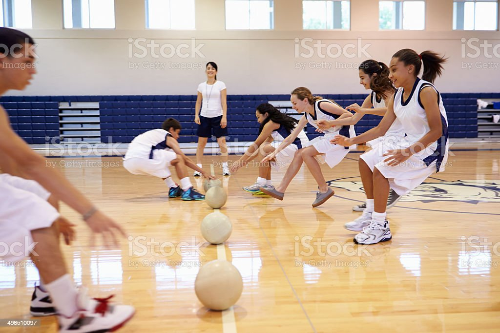 High School Students Playing Dodge Ball In Gym stock photo