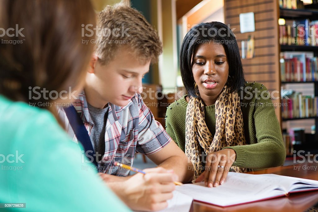High school students studying together in modern public library stock photo