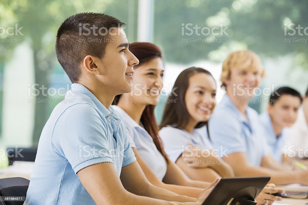 High school students wearing uniforms, using technology in class royalty-free stock photo
