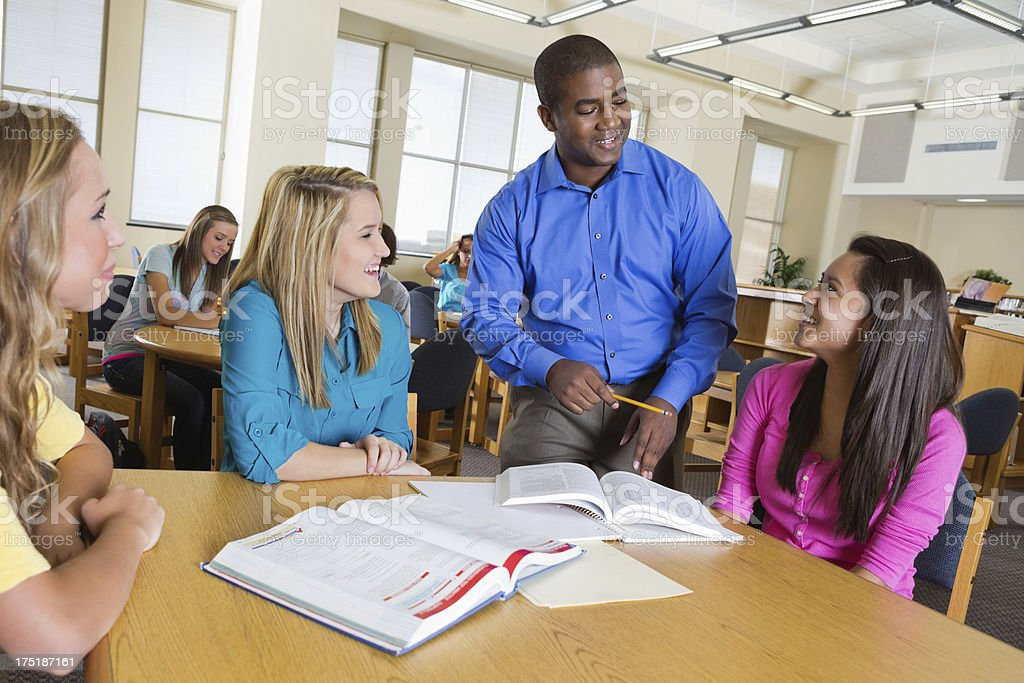 High school teacher assisting study group in library royalty-free stock photo
