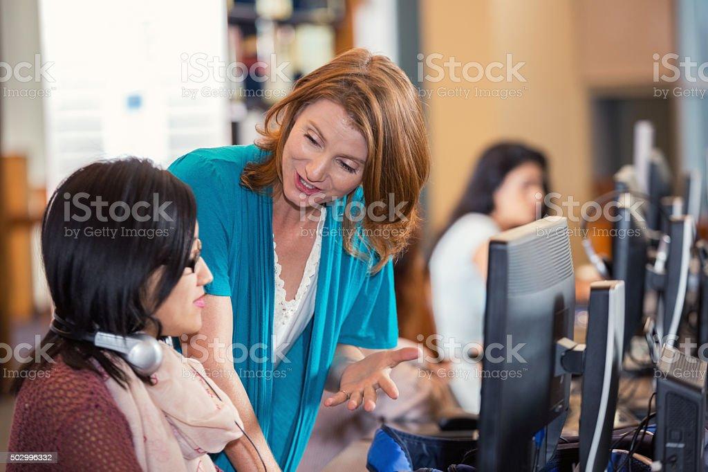 High school teacher helps student in computer lab stock photo