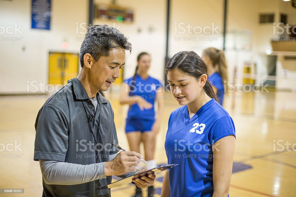 High school volleyball player talking with coach stock photo
