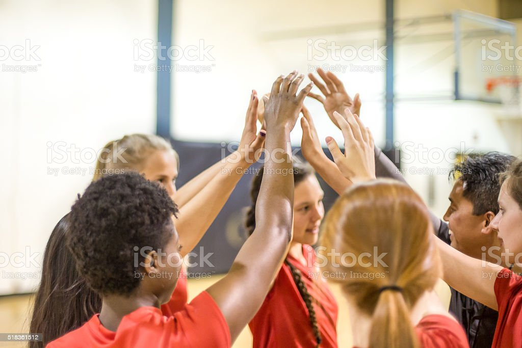 High school volleyball players in team huddle stock photo