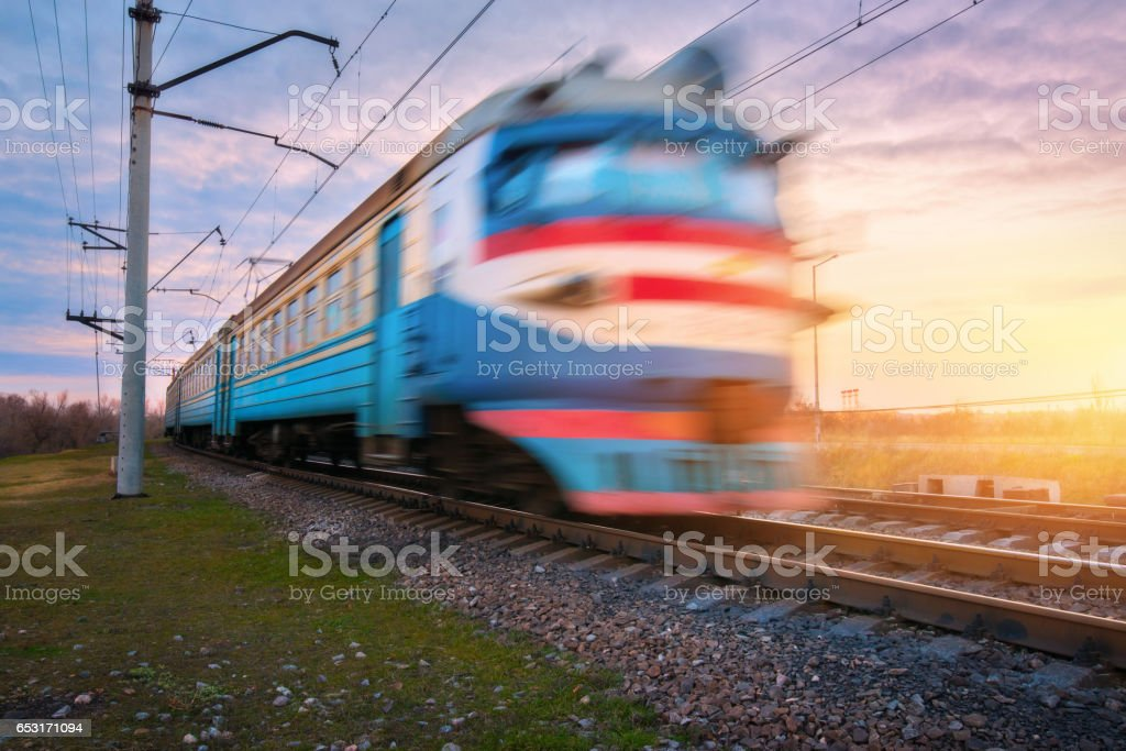 High speed passenger electric train in motion on railroad at sunset. Blurred old commuter train. Railway station against blue sky. Railroad travel, railway tourism. Rural industrial landscape. Concept stock photo