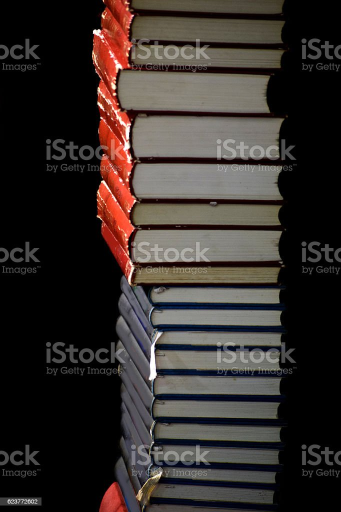 High stack of red and blue books on black background stock photo