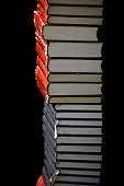 High stack of red and blue books on black background