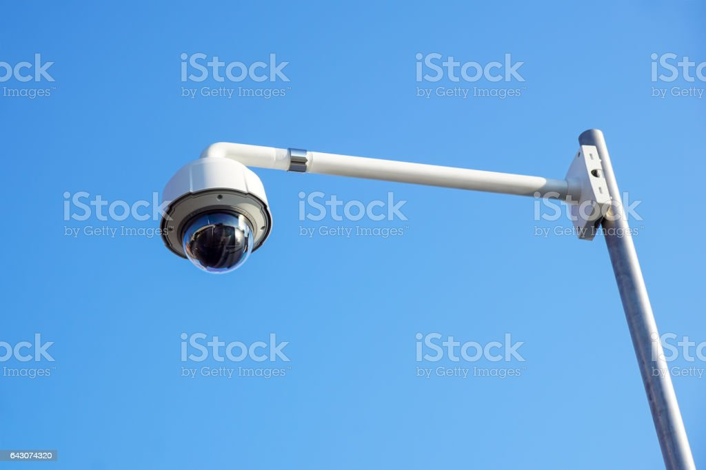 High tech overhead security camera with blue sky. stock photo