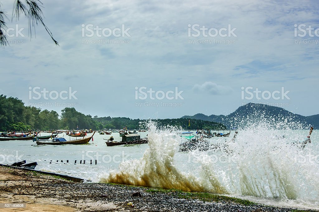 High tide waves flood over beach wall, Phuket, Thailand stock photo