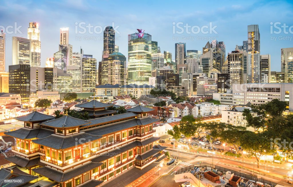 High view of Singapore skyline with skyscrapers and Tooth Relic Temple at blue hour - World famous top south east Asia destinations - City panorama on vivid warm filter with nightscape color tones stock photo