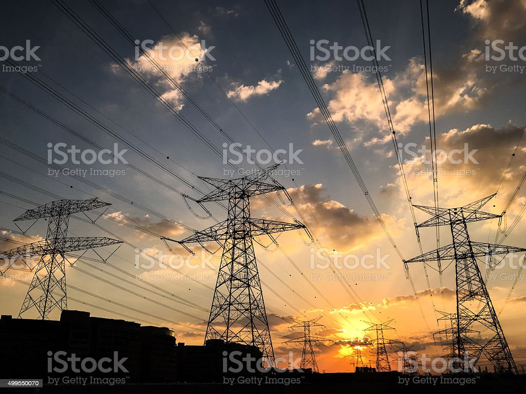 High Voltage Lines, electricity pylon with brightly lit sky stock photo