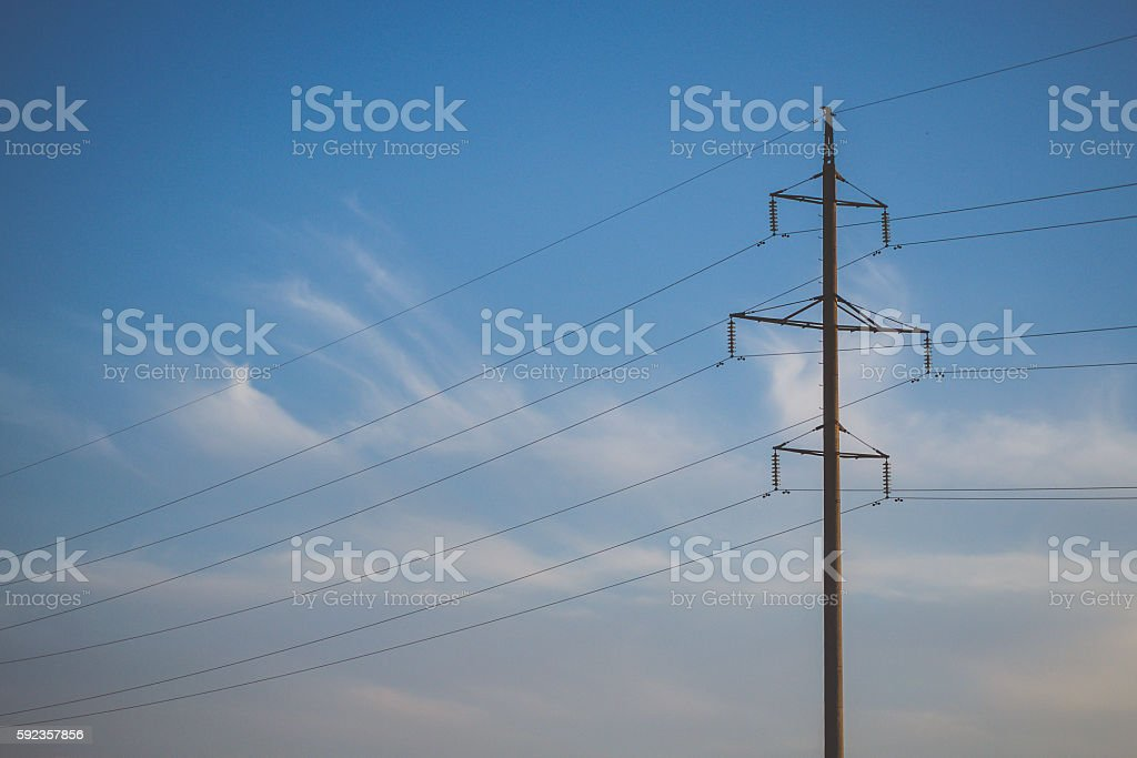 High voltage pillars on the background of cloudy sky stock photo