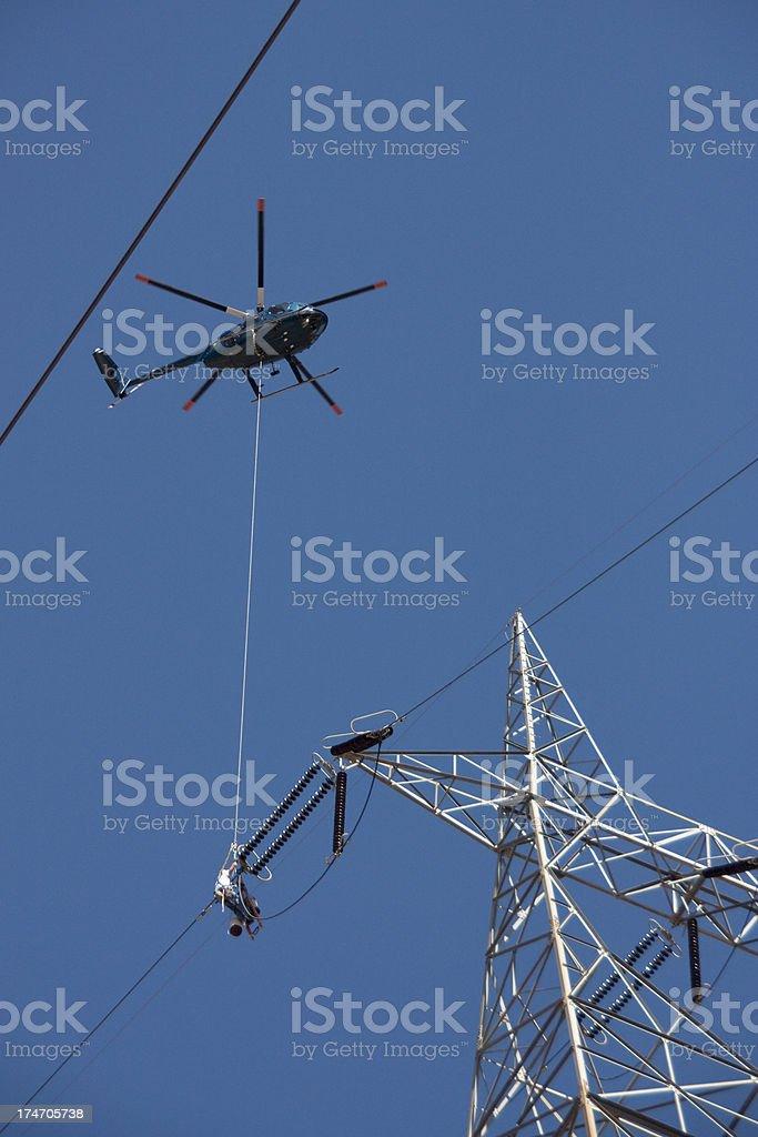 Entretien de la ligne électrique haute tension avec l'assistance d'un hélicoptère photo libre de droits