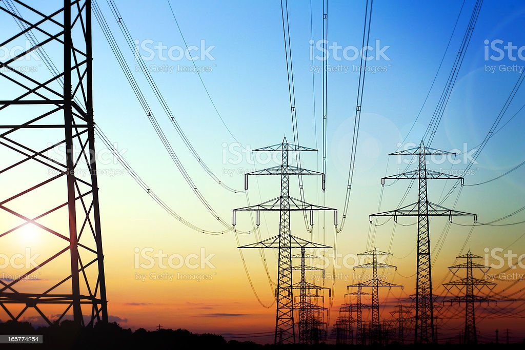 High voltage pylons in the evening sun stock photo