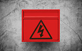 High voltage sign symbol, on red electronic box on concrete