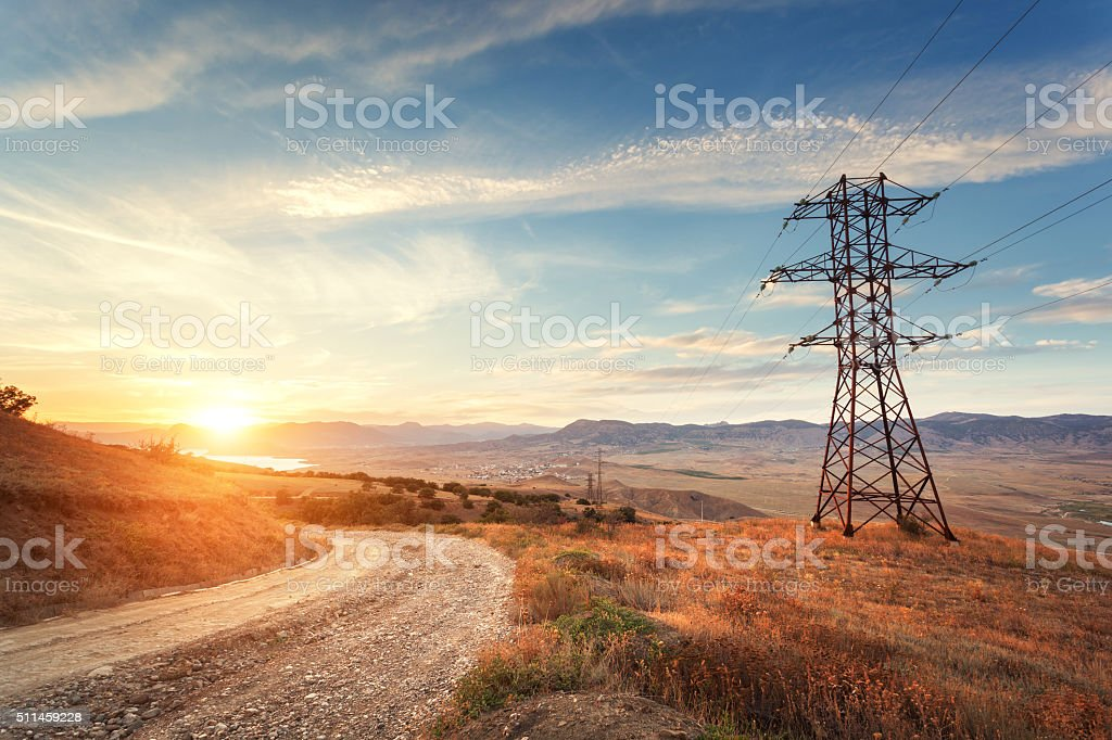High voltage tower in mountains at sunset. Electricity pylon system stock photo