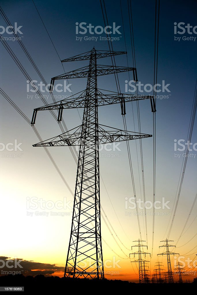 high voltage towers in atmospheric sunset royalty-free stock photo