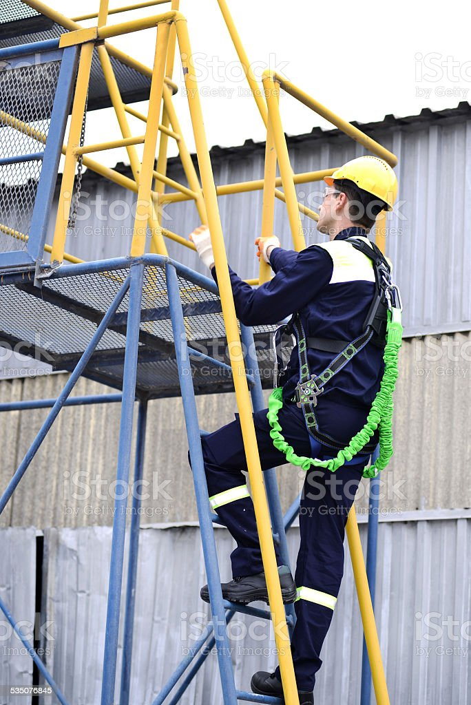 High worker climbing  scaffolding stock photo