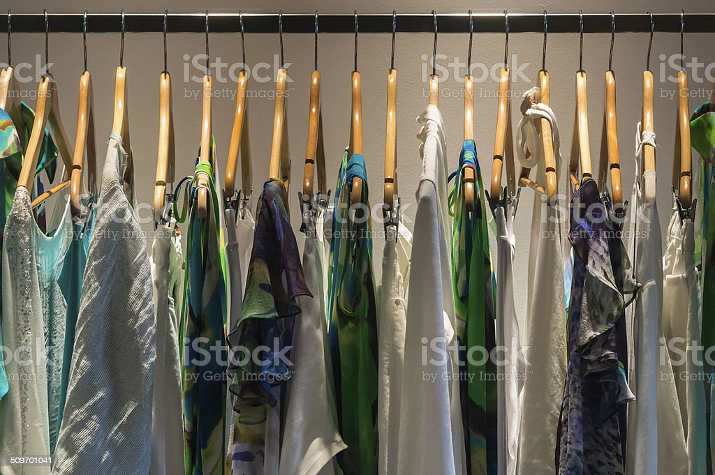 High-class women's clothes hangs in a row from a metal rod. stock photo