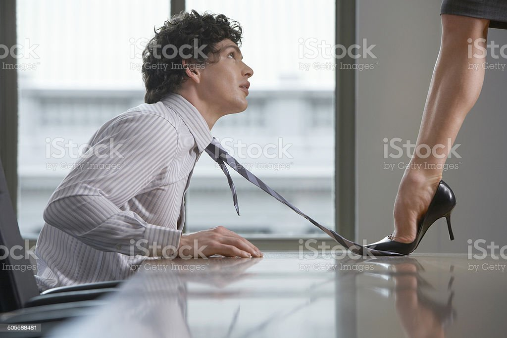 Highheeld Businesswoman Stepping On Businessman's Tie stock photo