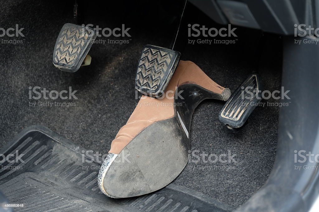 high-heeled shoe stuck under brake stock photo