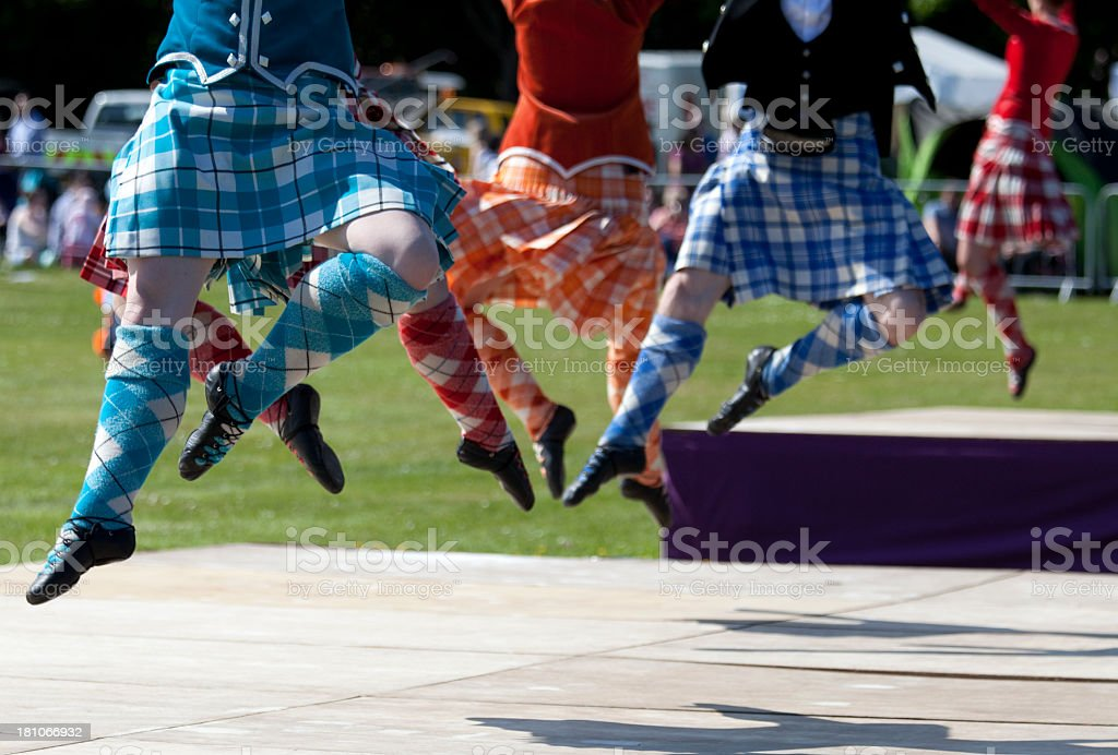 Highland dancers jumping up wearing plaid skirts stock photo
