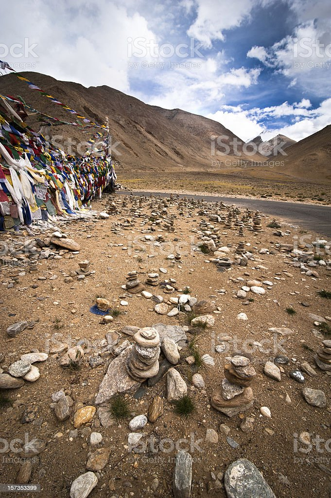 Highland road pass with stone pyramid and Buddhist praying flags stock photo