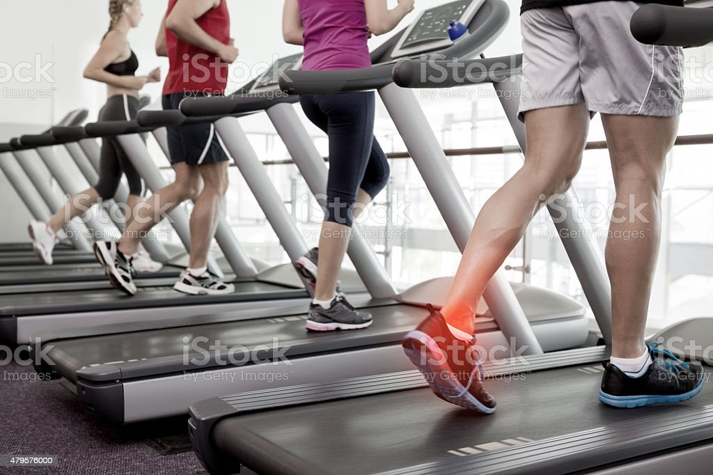 Highlighted ankle of man on treadmill stock photo