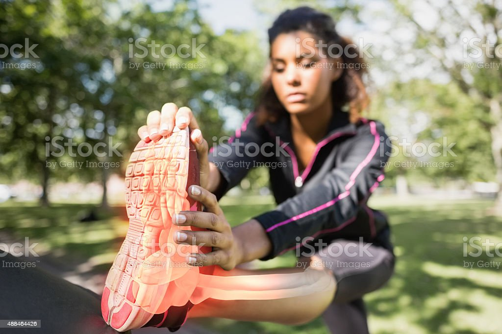 Highlighted ankle of stretching woman stock photo