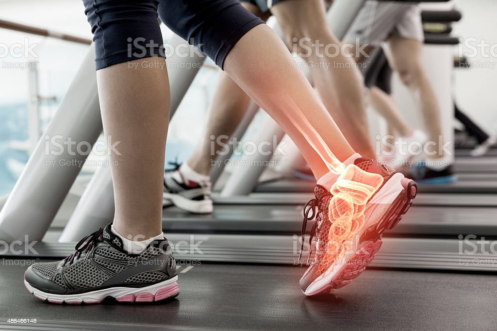 Highlighted ankle of woman on treadmill stock photo