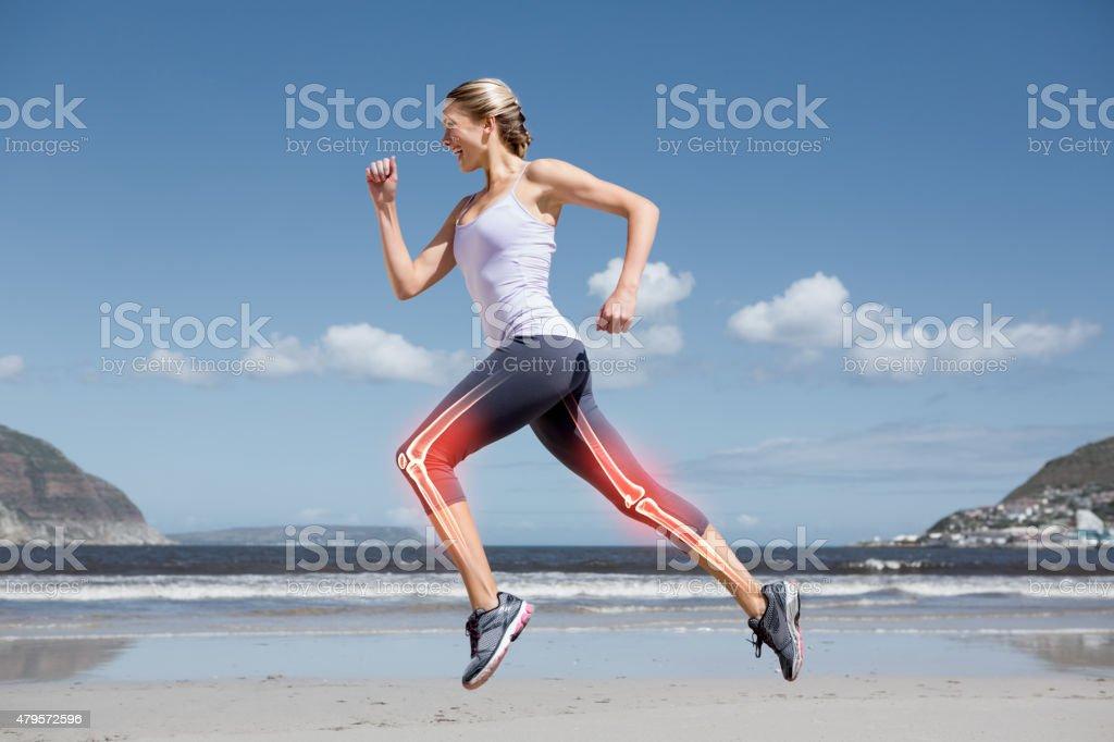 Highlighted leg bones of jogging woman on beach stock photo