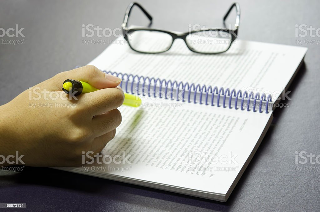 Highlighter pen with hand on the book stock photo