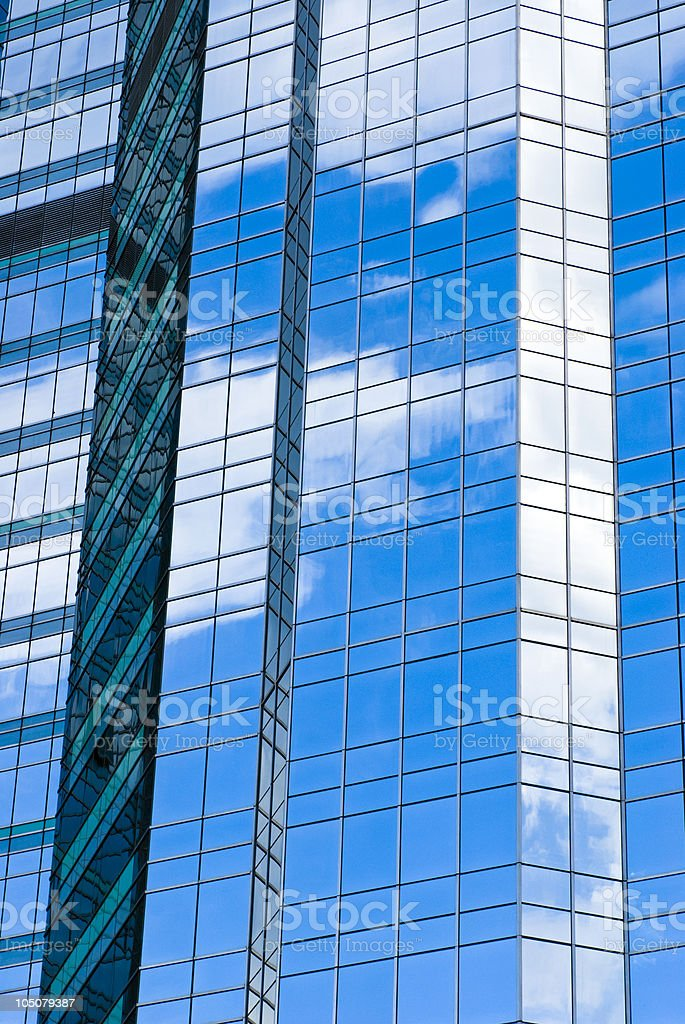 Highrise glass building with sky and clouds reflection stock photo