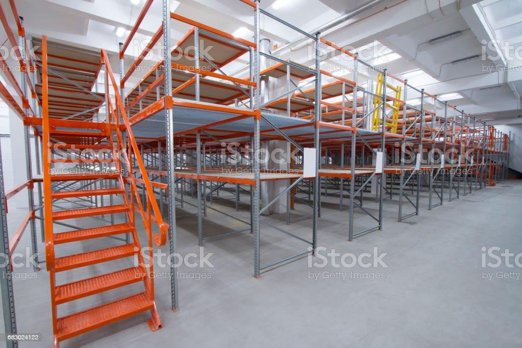 High-rise metal racks with ladder. Mezzanine shelves. stock photo