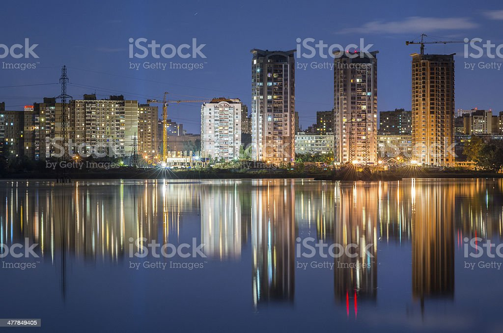 High-rise residential buildings near the lake at night with lights royalty-free stock photo