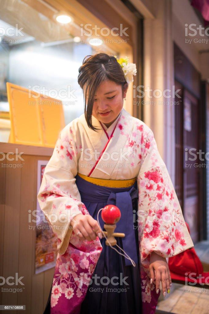 High-teen girl in Hakama traditional cloth playing kendama stock photo