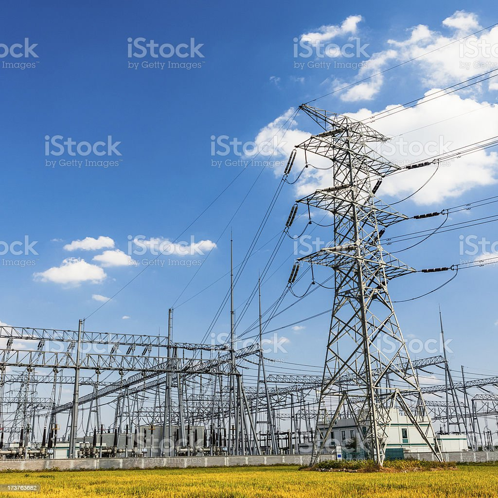 High-voltage power pylons and substation, blue sky royalty-free stock photo
