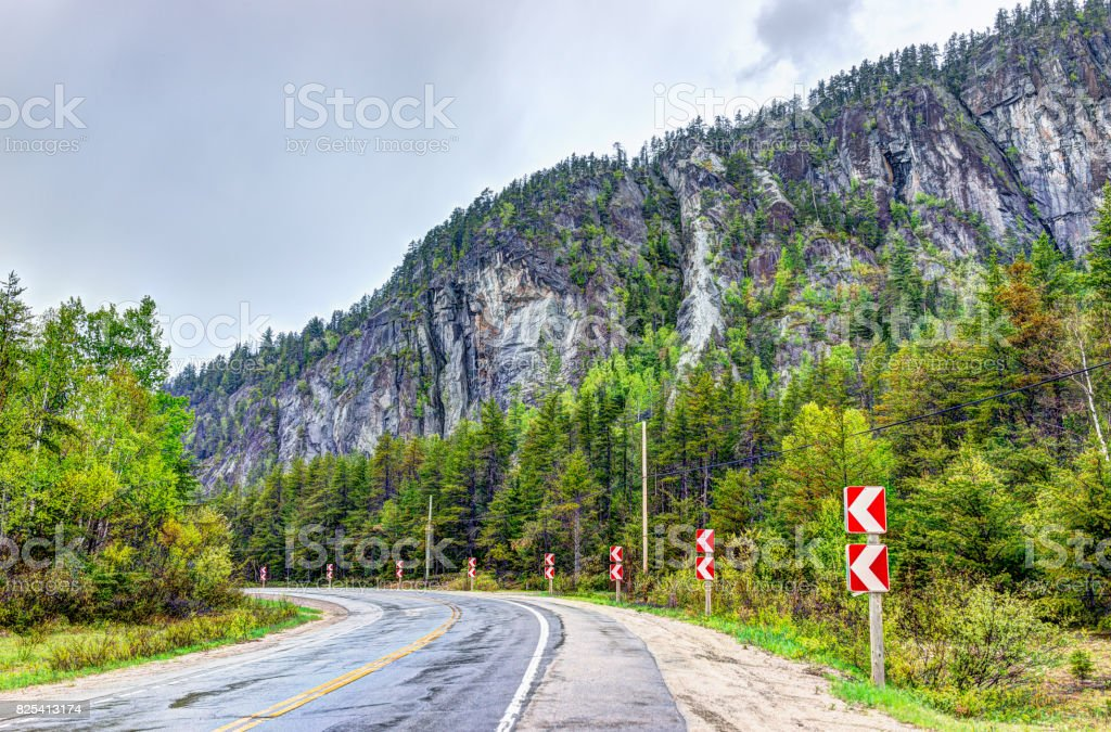 Highway road in stormy misty and foggy weather in mountain Charlevoix region of Quebec, Canada with turn stock photo
