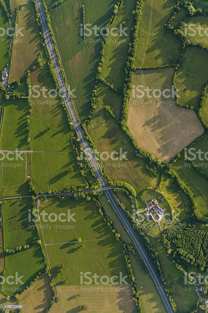 Highway slicing through idyllic rural landscape fields farms aerial view royalty-free stock photo