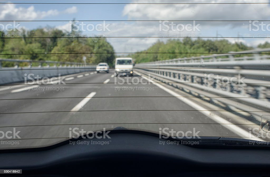 Highway traffic from the rear window stock photo
