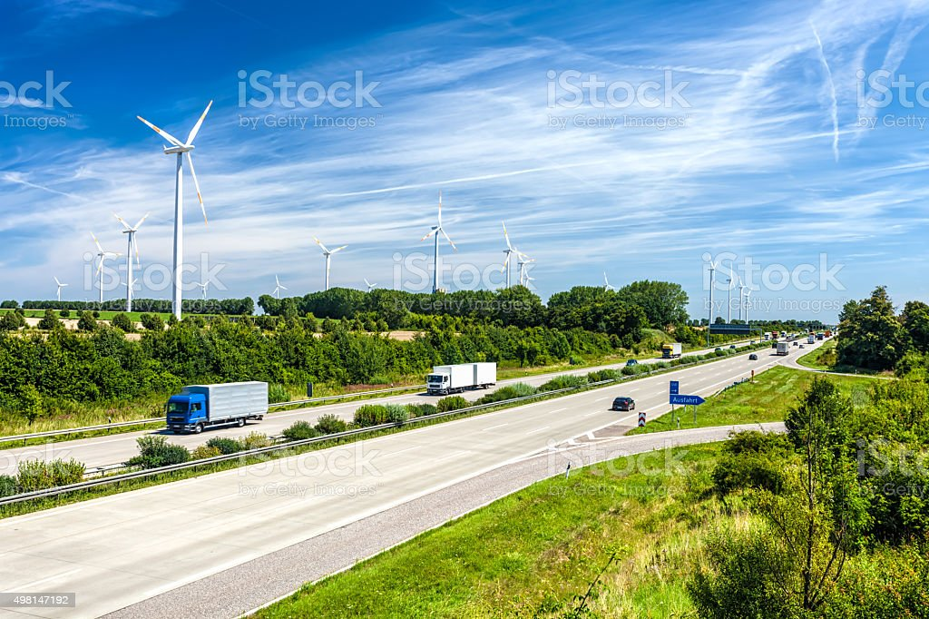 Highway traffic in Germany. Wind Energy in the background stock photo