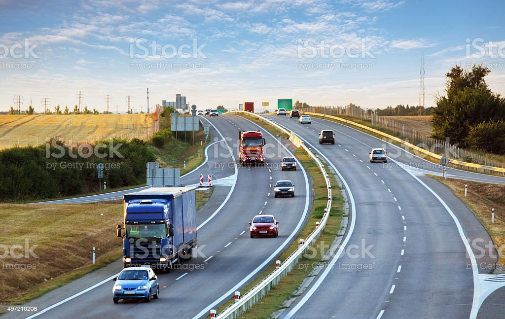 Highway traffic in sunset with cars and trucks stock photo