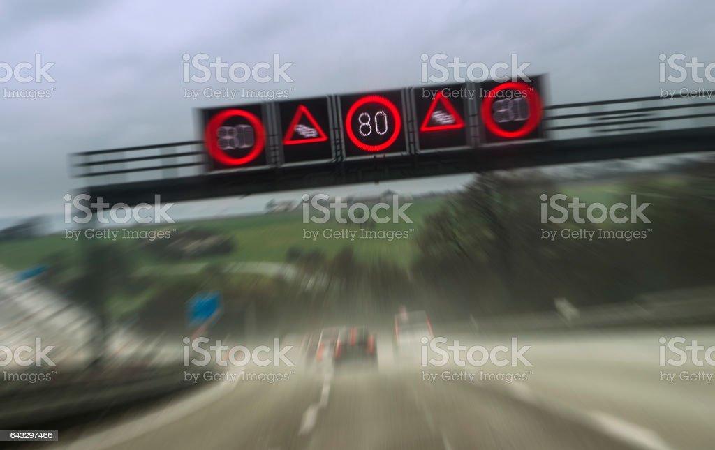 Speeding vehicles on highway, car window with rain drops