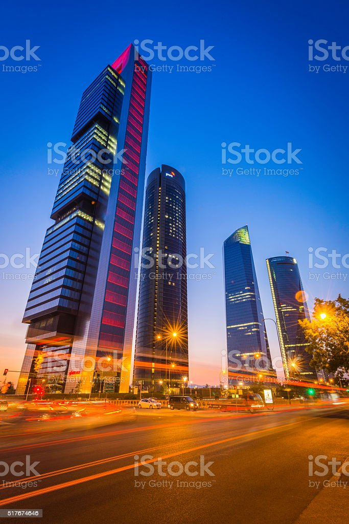 Highway traffic zooming past futuristic skyscrapers Cuatro Torres Madrid Spain stock photo