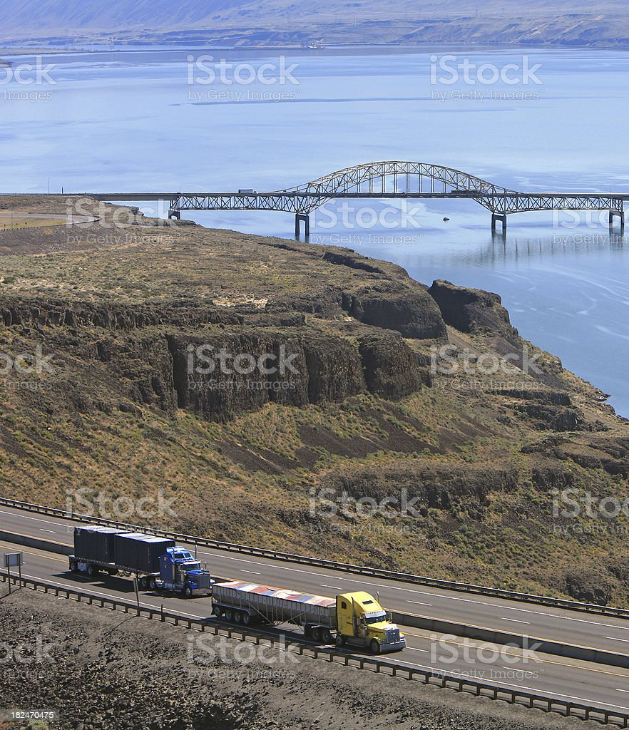 Highway Transportation With Two Semi Trucks In Foreground royalty-free stock photo