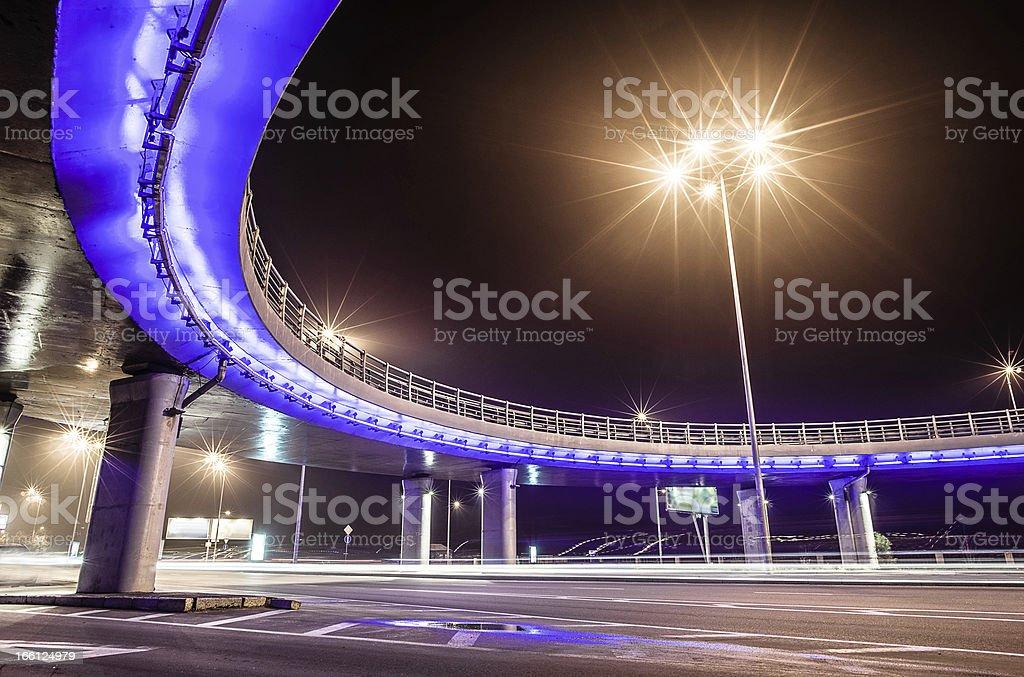 Highway under the bridge illuminated at night royalty-free stock photo