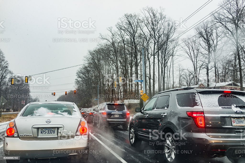 Highway with cars during snow waiting for traffic light stock photo