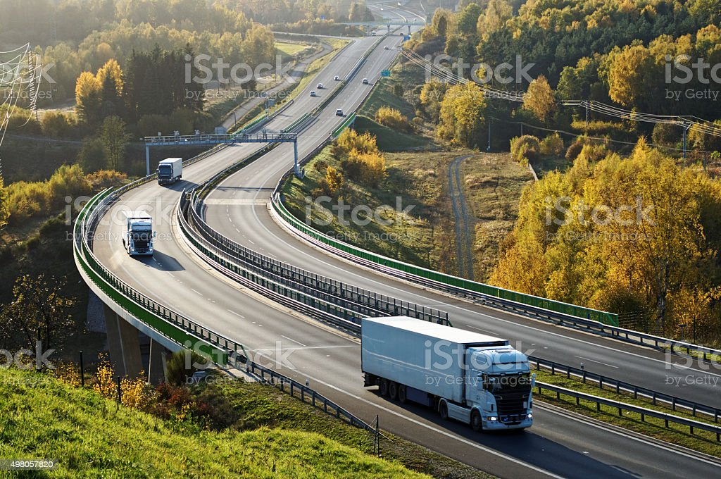 Highway with electronic toll gates in autumn woodland. stock photo