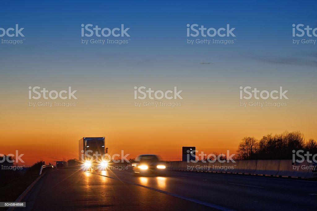 Highway with oncoming trucks and a car after sunset stock photo