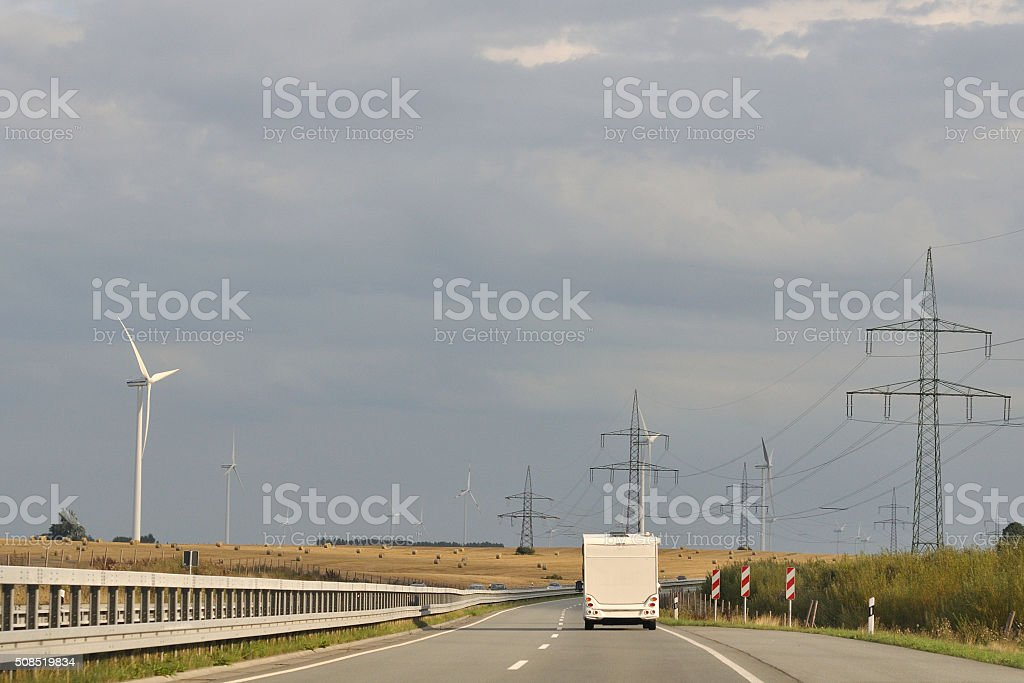 Highway with Power Lines and Wind Turbines stock photo