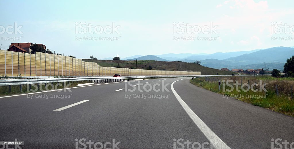 Highway with protective fence turning right by the village stock photo